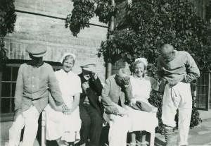 Sygeplejersker og patienter på en bænk i solen. Året er 1938.