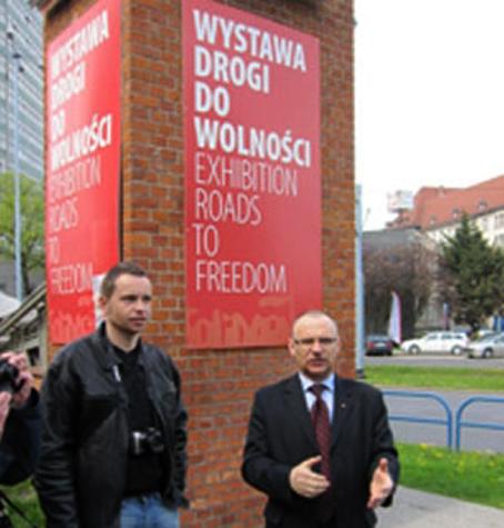 """Radek Krajewicz fra den polske ambassade i Danmark sammen med Solidarnocs-veteranen Jerzy Borowczak foran nedgangen til Solidaritets-museet i Gdansk. De første skud i den anden verdenskrig blev affyret i Gdansk, det daværende Danzig, da et tysk krigsskib om morgenen den 1. September 1939 åbnede ild mod den polske fæstning Westerplatte. Godt 40 år senere, 14. August 1980, skrev Gdansk sig atter ind i verdenshistorien, da arbejderne på Lenin-skibsværftet gik i strejke. Først i protest mod fyringen af en afholdt kollega, senere for at få opfyldt 21 krav, hvoraf de første var: Frie fagforeninger, strejkeret, ytringsfrihed, løsladelse af politiske fanger…. Strejken blev startskuddet til den udvikling, der førte til kommunismens fald og Østeuropas frihed. """"Det begyndte her"""" er titlen på en bog om Polens rolle i skabelsen af nutidens Europa. Og det var for med egne øjne at se stederne, hvor det begyndte, at en flok på 27 medlemmer af veteranklubben i maj besøgte de historiske mindesmærker i det nordlige Polen. Vi så fæstningen Westerplatte (nu mindepark), en primitiv bunker fra verdenskrigen, jernbanevognene, der transporterede polakker til Rusland, kopier af de landsforvistes usle træhuse i Sibirien, Lenin-værftets hovedindgang, Solidaritetspladsen med monumentet over de døde og museet """"Veje til friheden"""" med de originale træplader med de 21 krav. Vi mødte centrale figurer fra solidaritetskampen, deriblandt Jerzy Borowczak, der som ung værftsarbejder var med til at sætte strejken i gang sammen med Lech Waleza. Derudover besøgte vi regionens største avis, Dziennik Baltycki, gik i operaen, oplevede det genopbyggede Gdansks smukke gader og pladser og kørte ud i det polske forårslandskab, der mange steder minder meget om Danmark med lysegrønne bøgeskove og anemoner. Guiden forklarer foran Solidarnosc-monumentet i Gdansk Hjemturen gik over kystbyerne Sopot og Gdynia med færgen til Karlskrona i Sverige, hvor veteranerne fik en sagkyndig rundvisning i den historiske flådehavn, d"""