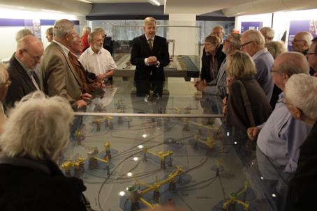 Veteranerne samlet omkring Nordsøolien (i model på firmaets museum) mens Henning Morgen fortæller om den lidt tøvende måde firmaet gik ind i oliebranchen. Foto: Finn Hillmose.
